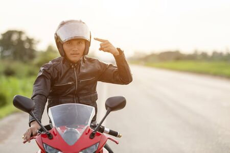 Handsome motorcyclist wear leather jacket and holding helmet on the road. Safe ride and transportation concept Stok Fotoğraf