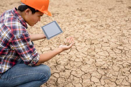 Joven ingeniero asiático trabajando en el sitio de la presa y revisando el suelo para ver el problema de la sequía