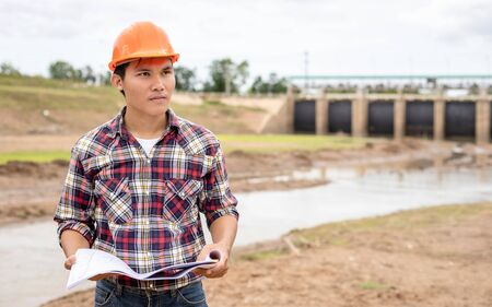 Asian young engineer working on site at the dam and control while excavator digging the earth
