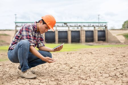 Asian young engineer working on site at the dam and checking the soil to see drought problem Stok Fotoğraf