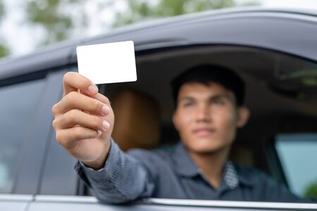Young asian man sitting in the modern car and holding blank of white card. For car rental or car business concept