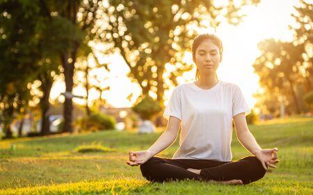 Donna abbastanza asiatica che fa esercizi di yoga nel parco. Utilizzato per rilassarsi e un sano concetto Archivio Fotografico