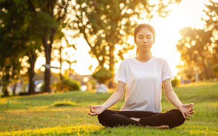 Pretty asian woman doing yoga exercises in the park. Used for relax and healthy concept Stock Photo