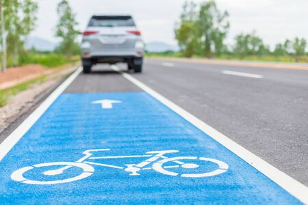 Modern SUV car running on asphalt road / bicycle lane and tread on white bicycle sign