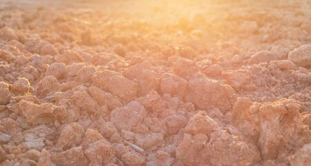 Heap of dry soil and rough mud in construction site. Shoot in sunset time with sunlight and lens flare effect