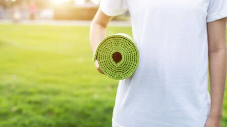 Pretty asian holding green yoga mat and prepare for doing yoga exercises in the park. Used for relax and healthy concept