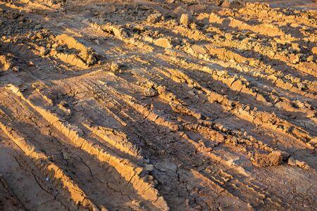 Wheel track on wet soil or mud.