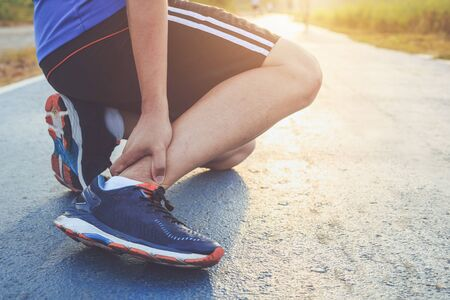 Injury from workout concept : The asian man use hands hold on his ankle while running on road in the park. Focus on ankle. Stok Fotoğraf