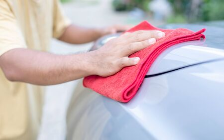 Hand of people using red cloth to cleaning body of SUV car. Stok Fotoğraf