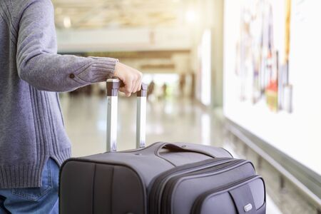 Young tourist walking and pull luggage at the airport. Travel and advertising concept
