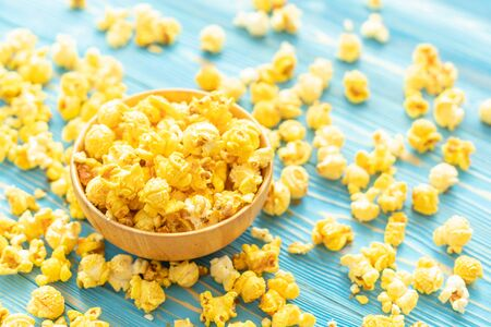 Top view yellow popcorn on blue wooden plank background. Food or snack concept