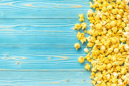 Top view yellow popcorn on blue wooden plank