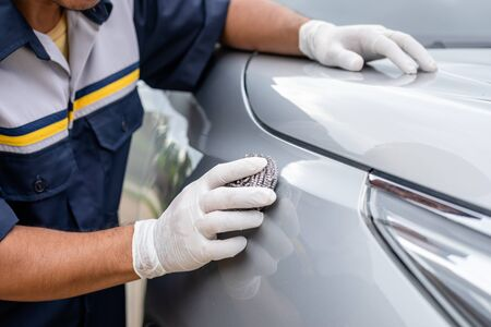 Hand of people using stainless steel wool to polishing the surface of car body. Wrong cleaning or washing car concept
