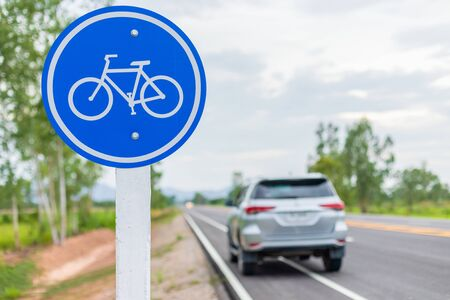 Modern SUV car running on asphalt road  bicycle lane and tread on white bicycle sign
