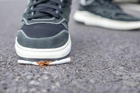Asian man destroy cigarette by foot. Stop smoking in public area concept