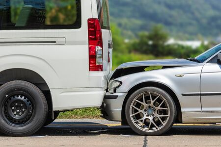 Car accident involving two cars on the road. Back side of van and front of siver car get damaged by accident. For car repair concept