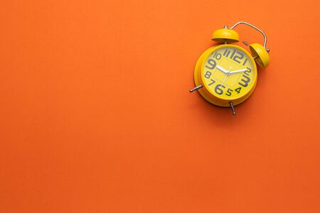 Top view yellow alarm clock on the middle of orange background