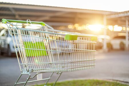 New supermarket trolley on the street and blur of car in parking lot. Shopping or purchasing concept Standard-Bild