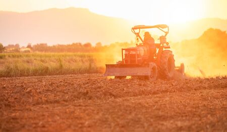 Thai farmer on big tractor in the land to prepare the soil for rice or corn growth season in Thailand
