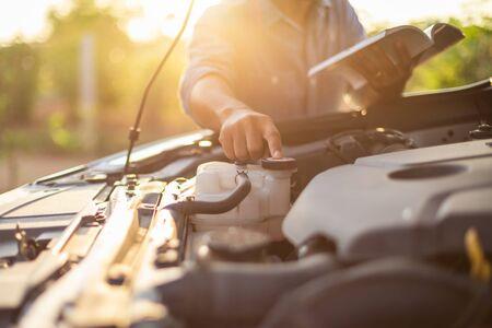 Uomo asiatico che tiene e legge il manuale dell'utente dell'auto o le istruzioni per l'utente per controllare o riparare il motore dell'auto moderna. Manutenzione o assistenza dell'auto prima di guidare il concetto Archivio Fotografico