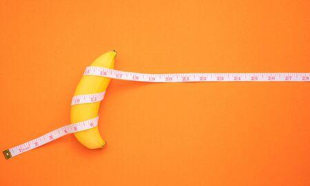 Nahaufnahme gelbe Banane mit Maßband auf orangem Hintergrund. Männer Penisgrößenkonzept mit leerem Freiraum für Text oder Design. Ansicht von oben