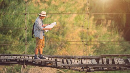 Asian tourist man walking on the old and broken wood bridge. Risks of travel concept 免版税图像
