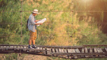 Hombre turista asiático caminando sobre el puente de madera vieja y rota. Riesgos del concepto de viaje Foto de archivo