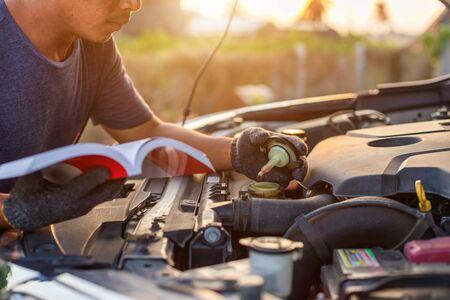 Asiatischer Mann, der das Benutzerhandbuch oder die Bedienungsanleitung des Autos hält und liest, um den Motor des modernen Autos zu überprüfen oder zu reparieren. Autowartung oder Service vor dem Fahrkonzept Standard-Bild