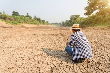 Asian farmer stand in the dry river and looking to empty water in Sukhothai. For drought season concept