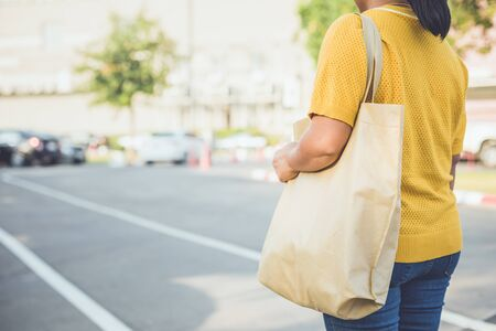 Woman using brown cotton bag in shopping center to replace plastic bag usage Stock fotó