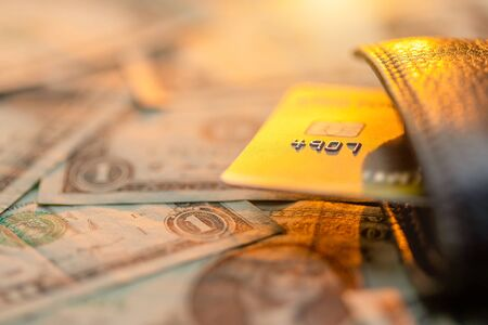 Close up credit card in black leather wallet on top of US dollar banknote. For business and financial concept