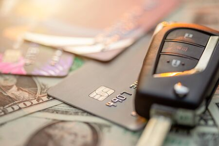 Close up new car keys, credit card and US dollar banknote on wooden table. Car purchase or car rental concept 스톡 콘텐츠