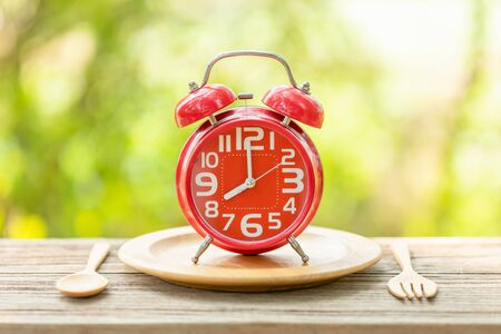 Close up red alarm clock, Fork, and spoon on wooden table with green outdoor nature blur background. Eight o'clock, Time for eating concept
