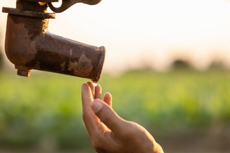 Close up hand of farmer waiting for water from vintage outdoor water pump. For drought season concept Stock Photo
