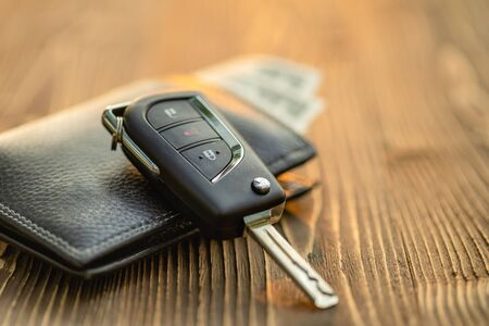 Close up new car keys with US dollar banknote on wooden table. Car purchase or car rental concept