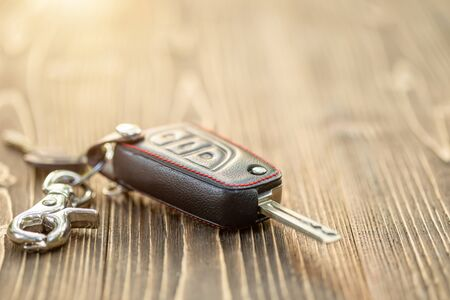 Close up new car keys with black leather cover on wooden table Foto de archivo - 140183756