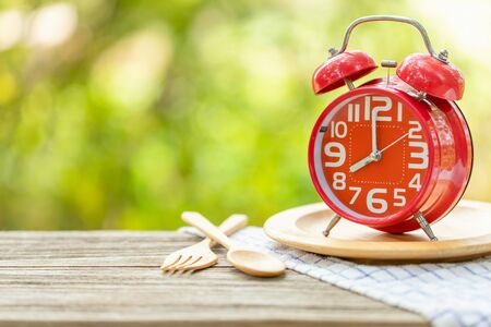 Close up red alarm clock, Fork, and spoon on wooden table with green outdoor nature blur background. Eight o'clock, Time for eating concept Zdjęcie Seryjne