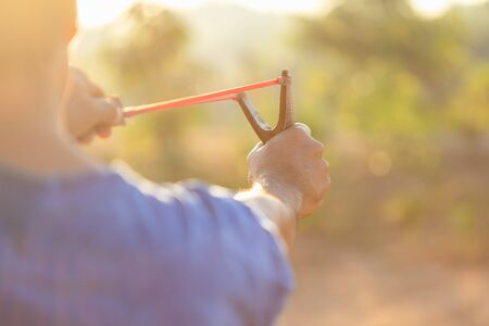 Close up man playing slingshot or catapult in morning time with sunlight effect