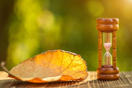 Close up vintage hourglass or sandglass with dry tree leaf on wooden table, Green nature blur background