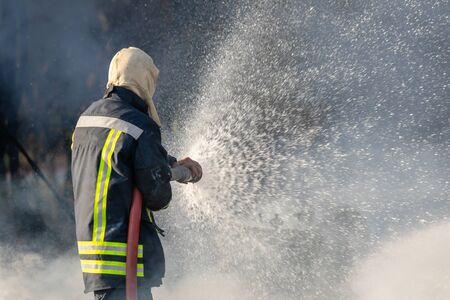 Fireman or firefighter spraying water from big water hose to prevent fire