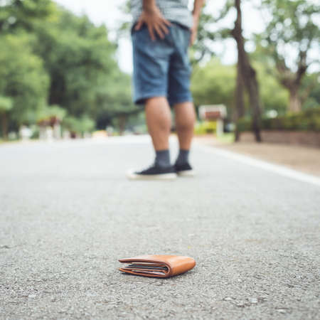 Asian man lose brown wallet on the road in tourist attraction. Losing wallet concept. Focus on wallet Banque d'images