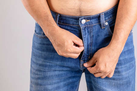 Close up fat man trying to zipping his blue jeans pant on grey background