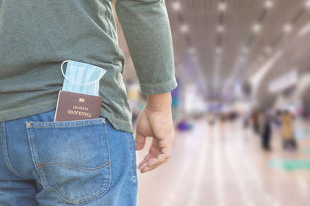 Close up passport and new protective mask in jeans pocket. Safety for travelling concept. Interior shooting with airport space blur background