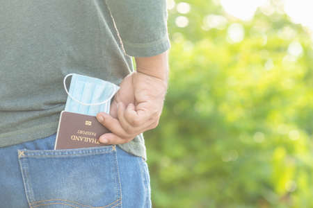 Close up passport and new protective mask in jeans pocket. Safety for travelling concept. Outdoor shooting with green space blur background Stockfoto