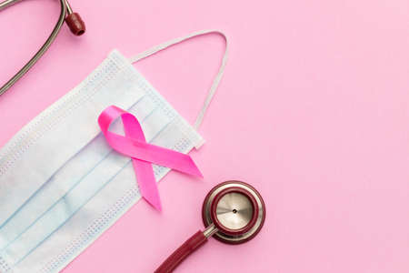 Breast Cancer concept : Top view pink ribbon, red stethoscope and protective mask symbol of breast cancer campaign on pink background
