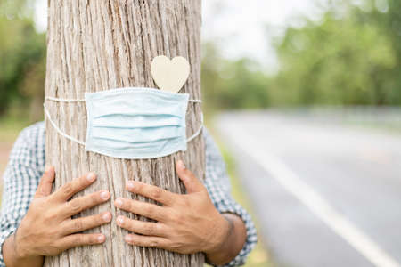 Tree hugging. Asian man giving a heart and a hug on big tree. Love tree and nature or environment concept