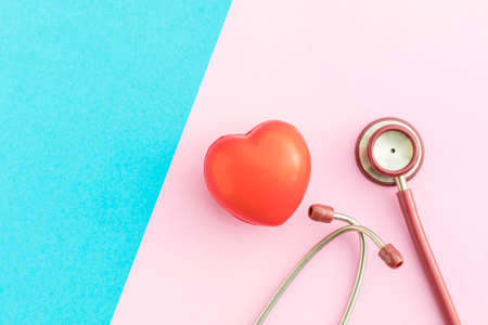 Top view red stethoscope and red heart shape on pink and blue background