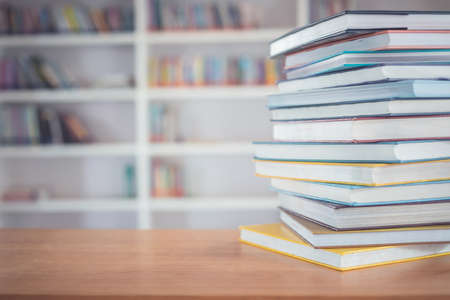 Close up book stack on the table in the library room and blurred space of bookshelf background Stockfoto
