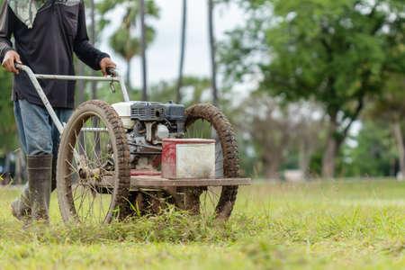 Thai worker mowing grass with machine in the public garden