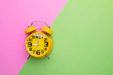 Top view old yellow alarm clock on bright color background Stockfoto